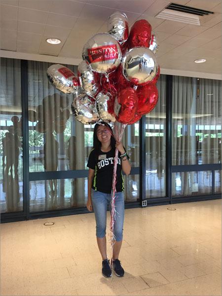 Ava holding Boston University balloons