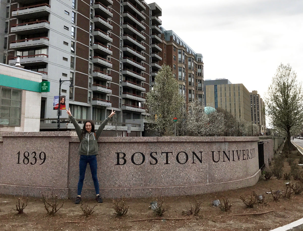 Minyu stands in front of BU sign