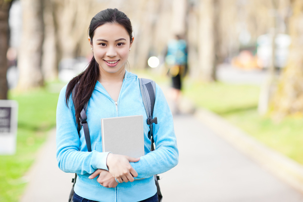 Smiling Asian student carrying iPad